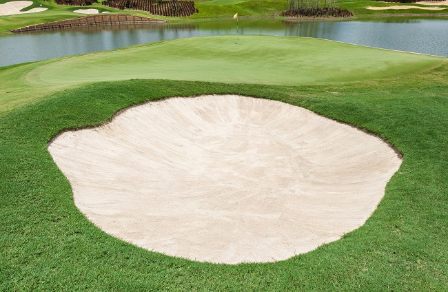 Sand bunker and clear lake on the beautiful golf course in Thailand.