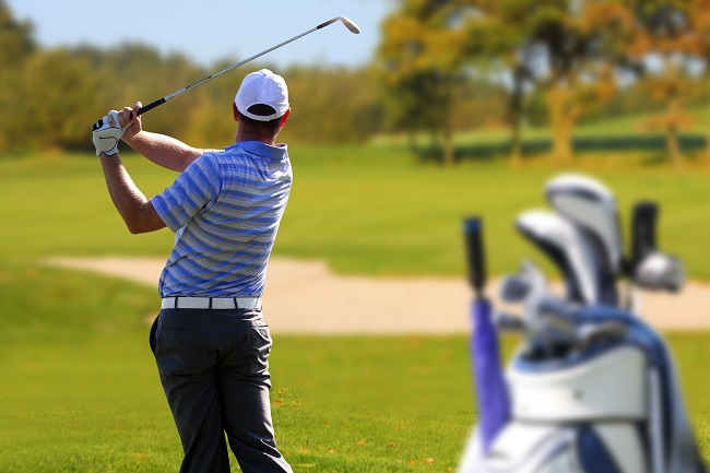 Man Finishing Golf Shot with Golf Bag and Bunker